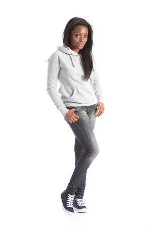 women in jeans: Relaxed standing pose from beautiful young black teenage girl, wearing grey hoodie sweater and blue jeans. Girl has long hair. Stock Photo
