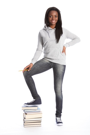 african education: On top of school work. Smiling and relaxed standing pose from beautiful young black teenage student girl, wearing grey hoodie sweater and blue jeans. Girl has one foot on top of a pile of books.