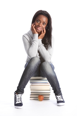 Beautiful black student girl on top of her school work. Smiling and sitting on a pile of books, girl is wearing grey hoodie sweater, blue jeans and sneakers. photo