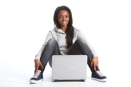 Beautiful black student girl sitting on floor with a laptop computer between her legs. She is dressed casually in blue jeans, grey hoodie sweater and blue trainers. photo