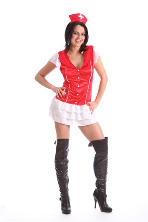 Beautiful young caucasian model wearing a sexy red and white fancy dress nurse costume with long black leather boots. Model has big happy smile on her face. photo