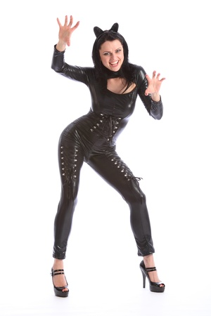 latex girl: Curvy figure of sexy young caucasian woman wearing a black pvc cat suit complete with ear head piece. Model is striking a fun cat pose with a big happy smile. Stock Photo