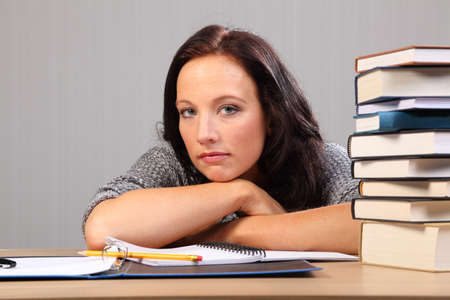 Beautiful caucasian student woman at home, looking tired from homework, sitting to her desk resting chin on hands. photo