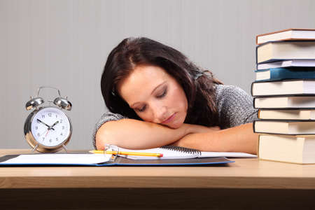 Beautiful caucasian student woman at home, tired from homework and falls asleep sitting to her desk. photo