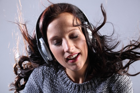 Lost in the music for a beautiful young woman, wearing silver headphones with her hair blowing upwards. photo