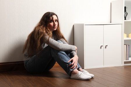 zenuwachtig: A nervous and frightened looking teenage girl sitting alone on the floor at home. Stockfoto