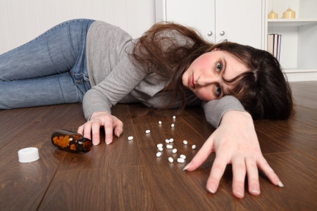 sobredosis: Joven tirada en el suelo en casa despu�s de una sobredosis de p�ldoras. Sus ojos est�n abiertas directamente desde c�mara y hay una botella de p�ldoras en el piso a su lado. Foto de archivo