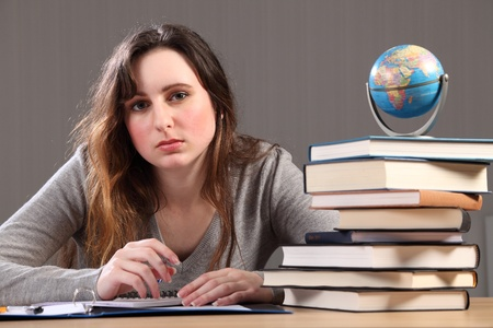 Teenage caucasian student girl at home, sitting to her desk studying geography with work books nearby and a globe of the world. Stock Photo - 9926313