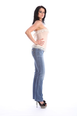 Sexy tall and healthy young woman wearing cream coloured corset with lace trimming, and blue denim jeans. Has stiletto peep toe shoes on her feet. photo