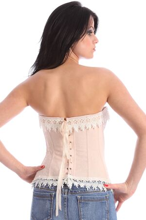 Beautiful young female fashion model posing with back to camera, wearing a cream coloured corset with lace trimming, and blue denim jeans. Stock Photo - 9926240