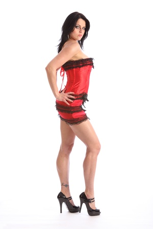 Sultry gaze from a sexy long legged beautiful young caucasian woman, wearing a black and red fashion corset and skirt, with lace trimming. Model wearing stiletto heels. Stock Photo - 9926237
