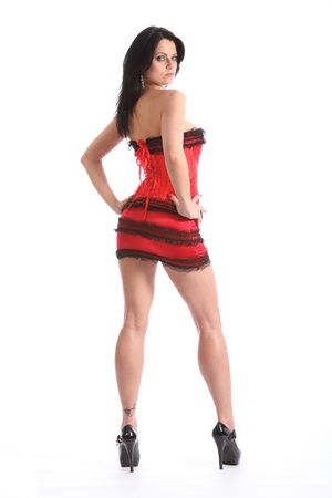 Sultry gaze from a sexy long legged beautiful young caucasian woman, wearing a black and red fashion corset and skirt, with lace trimming. Model wearing stiletto heels. Stock Photo - 9926236