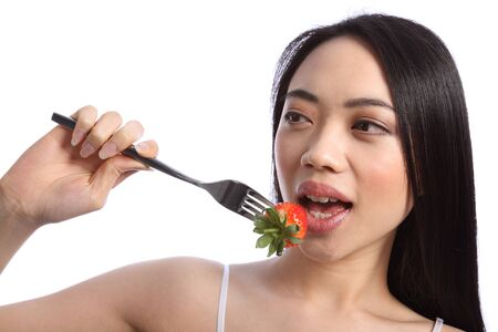 Exotic and beautiful young oriental girl, with long black hair, about to bite into a fresh strawberry fruit on a fork. Stock Photo - 9926248
