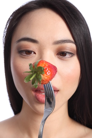 Going cross eyed, an exotic and beautiful young oriental girl, with long black hair ready to eat a fresh strawberry fruit on a fork. Stock Photo - 9926278