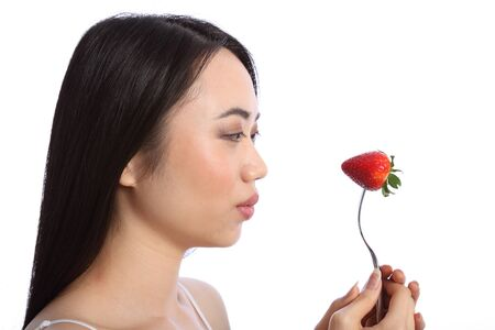 Beautiful young oriental teenager girl in profile, holding up a fresh red strawberry fruit on a fork. Stock Photo - 9926246