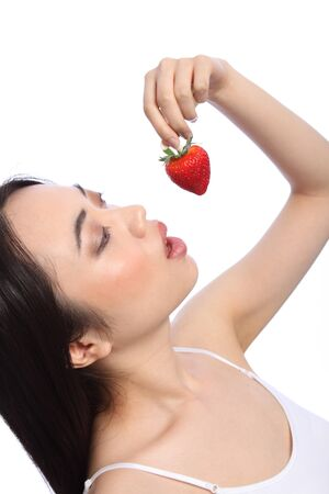 Beautiful sexy young oriental girl in profile, head tilted back about to eat a fresh red strawberry fruit. Stock Photo - 9926245