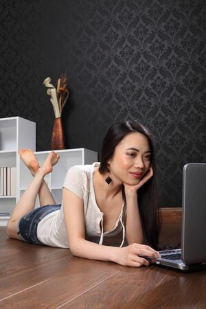 Beautiful smiling young chinese asian woman lying on the floor at home, surfing the internet and facebook with her laptop computer. photo