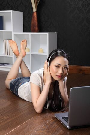 Headphones on listening to music, a beautiful young chinese asian girl lying on the floor at home, surfing the internet and facebook with her laptop computer. photo