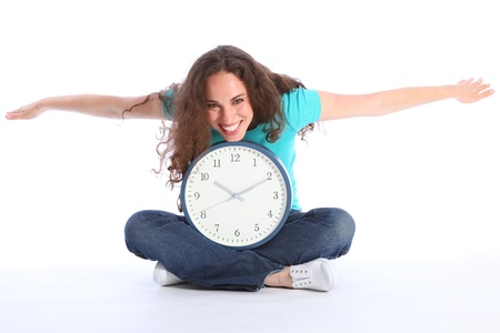 time flies: Time flies fun pose by beautiful young smiling woman holding a large clock. She has long brown hair and is wearing blue jeans and turqoise t-shirt sitting cross legged on floor.