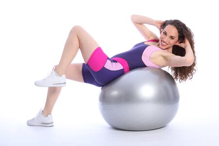 Beautiful young woman doing warm up fitness ball exercise routine. Woman has a happy smile and is wearing bright blue and pink sports clothes. photo
