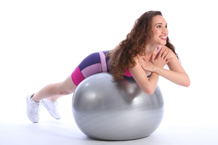 Beautiful brunette woman with big smile lying on top of fitness exercise ball for balance during workout. She is wearing bright blue and pink sports clothes and white trainers. photo