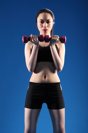 Beautiful young Asian Chinese girl working out with hand weights, wearing black sports bra and shorts, standing in blue studio. photo