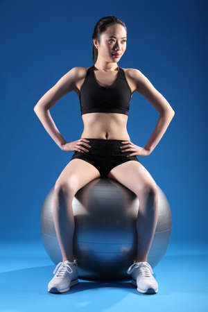 Concentrating on balance exercise, a beautiful young asian woman in sitting pose on fitness ball. She is wearing black sports clothes and white trainers. photo