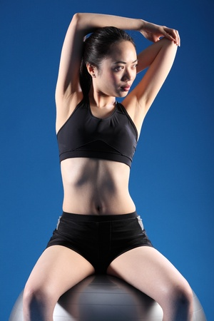 Concentrating on balance exercise while doing warm up stretch, a beautiful young asian woman in sitting pose on fitness ball. She is wearing black sports clothes and white trainers. photo