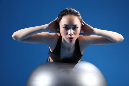 Back stretch during workout by a beautiful young oriental asian woman on fitness exercise ball. She is wearing black sports clothes. photo