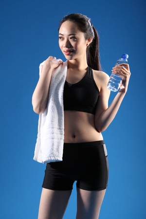 Happy and relaxed after a fitness workout, a beautiful Chinese Asian girl wearing a black sports outfit, standing with bottled water and a towel. photo