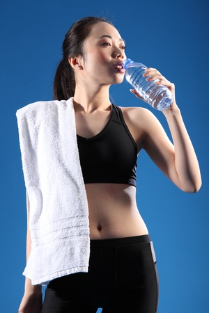 Happy and relaxed after a fitness workout, a beautiful Chinese Asian girl wearing a black sports outfit, standing drinking bottled water with a towel over her shoulder. photo