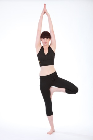 female pose: Yoga fitness demonstration of Tree Pose Vrksasana, by beautiful young healthy caucasian woman, wearing black fitness outfit.
