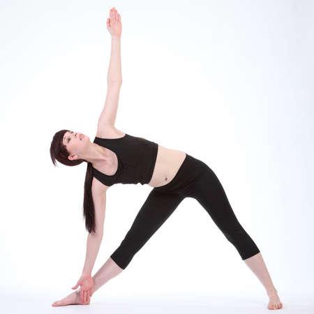 Beautiful fit caucasian girl demonstrating Revolved Triangle yoga pose Parivrtta Trikonasana, wearing black fitness outfit. photo