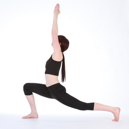 Yoga fitness demonstration Yoga Warrior One pose Virabhadrasana one, by beautiful young caucasian woman, wearing black fitness outfit. photo