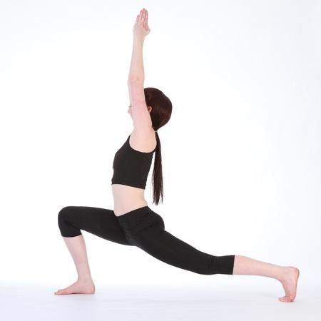 virabhadrasana: Yoga fitness demonstration Yoga Warrior One pose Virabhadrasana one, by beautiful young caucasian woman, wearing black fitness outfit.