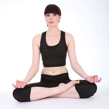 Yoga lotus pose padmasana by beautiful young caucasian woman wearing black fitness outfit photo