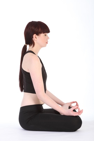 Side profile view of yoga lotus pose padmasana by beautiful fit caucasian girl wearing black fitness outfit photo