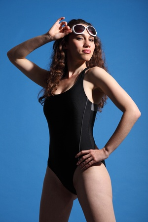Beautiful woman wearing black swimsuit and sun glasses standing outdoor in the warm sunshine against a blue sky. photo