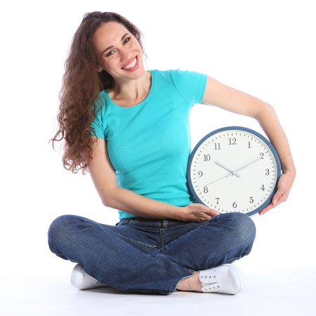long legged: Time on her side fun fun pose by beautiful young smiling woman holding a large clock. She has long brown hair and is wearing blue jeans and turqoise t-shirt sitting cross legged on floor. Stock Photo