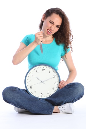 long legged: Killing time in a fun crazy pose by beautiful young woman holding a knife and large clock. She has long brown hair and is wearing blue jeans and turqoise t-shirt sitting cross legged on floor. Stock Photo