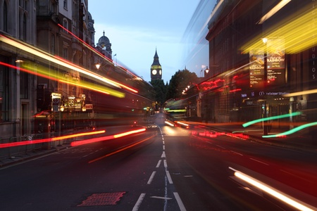 London england dawn breaking over the city of westminster, with the clock tower of Big Ben over the light trails of red london buses and cars on the street. photo