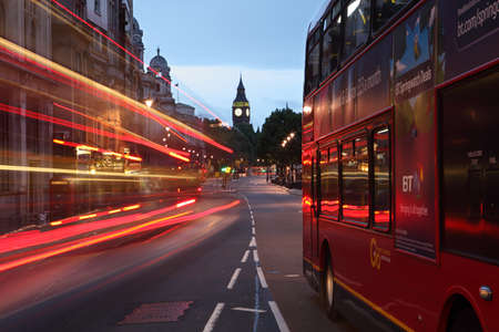 city lights: London england dawn breaking over the city of westminster, with the clock tower of Big Ben over the light trails of red london buses on the street. Stock Photo