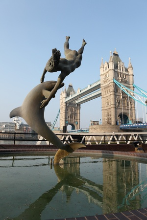 1973 Girl with a dolphin statue by David Wynne, near historic tourist attraction Tower Bridge over river Thames in London UK, capital city of England.