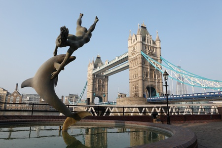 british girl: 1973 Girl with a dolphin statue by David Wynne, near historic tourist attraction Tower Bridge over river Thames in London UK, capital city of England.