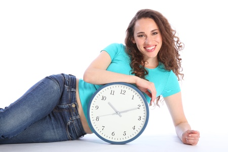 Time to relax and chill out pose by sexy smiling girl lying on the floor with a large clock. She has long brown hair and is wearing blue jeans and turqoise t-shirt. Stock Photo - 10034266