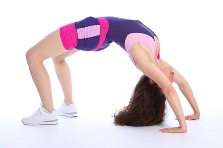leotard: Fit and healthy brunette woman in crab pose during fitness exercise routine. She is wearing bright blue and pink sports clothes and white trainers.