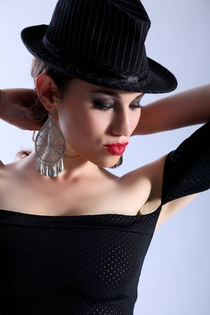 fedora hat: High fashion portrait of a beautiful caucasian woman, bright red lipstick and wearing a black hat. Model has dark eye shadow and dramatic make up.