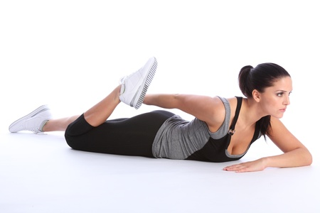thigh: Fit beautiful young woman concentrates lying on the floor, doing thigh stretch exercise during fitness workout. She is wearing a grey and black sports outfit with white trainers.