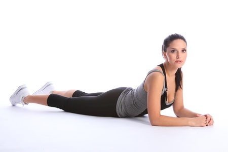 lycra: Fit beautiful young athletic woman lying on the floor wearing a grey and black sports outfit with white trainers. Stock Photo