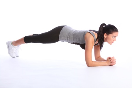 Fit beautiful young woman concentrates during floor exercise during fitness workout. She is wearing a grey and black sports outfit with white trainers. photo